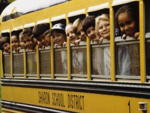 school children looking out school bus windows